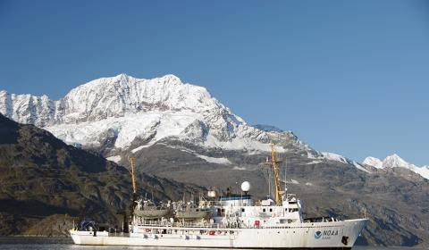 NOAA Ship on the water with a snowy mountain behind it.